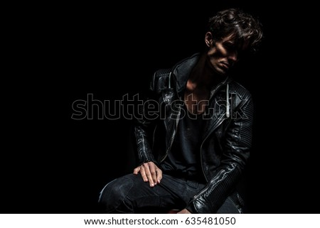 side view of a seated fashion model wearing leather jacket and looking away from the camera