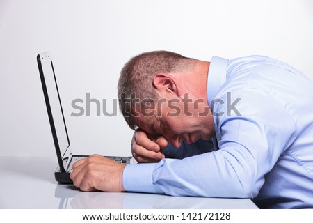 side view of a senior business man sleeping on his laptop. on gray background - stock photo