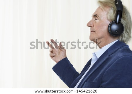 Side view of a senior businessman enjoying music with headphones