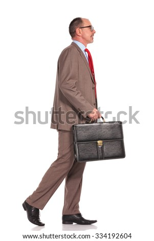 side view of a senior businessman holding suitcase and walking on white background - stock photo