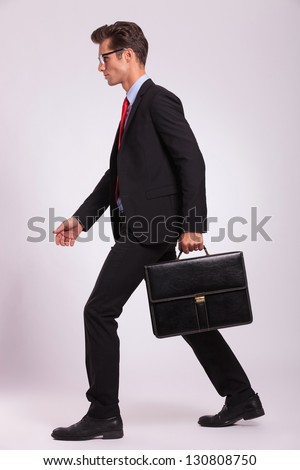 side view of a serious business man holding a briefcase and walking forward on gray background - stock photo