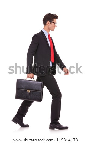 side view of a serious business man holding a briefcase and walking forward on white background - stock photo