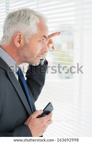 Side view of a serious mature businessman peeking in the office - stock photo