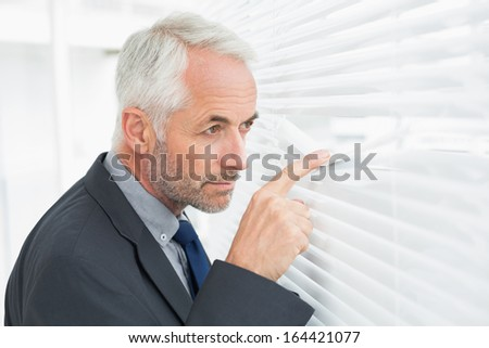 Side view of a serious mature businessman peeking in the office