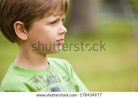 Side view of a serious young boy at the park
