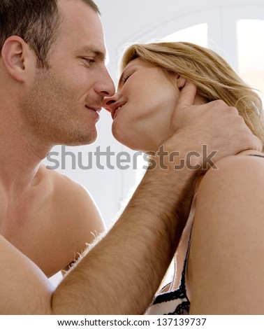 Side view of a sexy and attractive couple kissing in intimacy in a hotel bedroom.