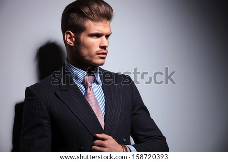 side view of a sexy young man in classic suit and tie holding his collar on gray background