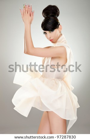 side view of a sexy young woman playing with her dress on studio background - stock photo