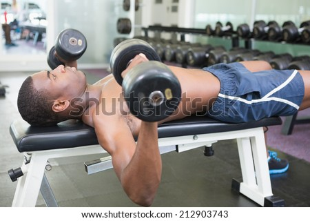 Side view of a shirtless young muscular man exercising with dumbbells in gym
