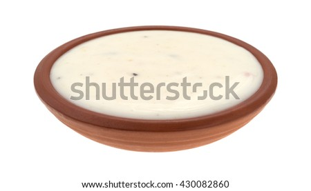 Side view of a small bowl of creamy Italian salad dressing isolated on a white background. - stock photo