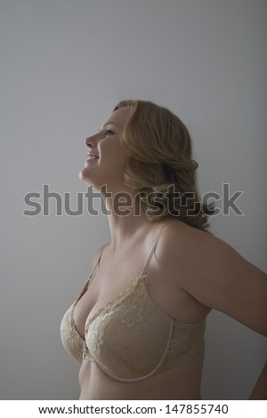 Side view of a smiling blond woman in bra against gray background - stock photo