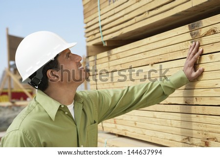 Side view of a smiling construction worker in hardhat inspecting lumber on job site - stock photo