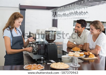 Side view of a smiling couple looking at waitress prepare coffee at the coffee shop