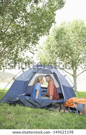 Side view of a smiling couple sitting face to face in tent - stock photo