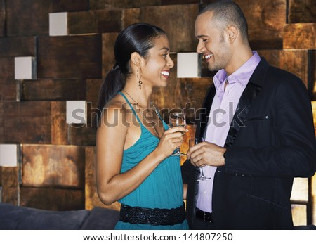 Side view of a smiling couple standing face to face with drinks in bar - stock photo