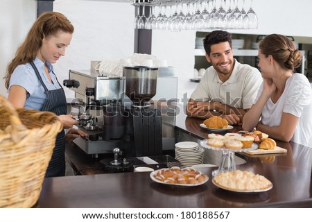 Side view of a smiling couple with female cafe owner at the coffee shop