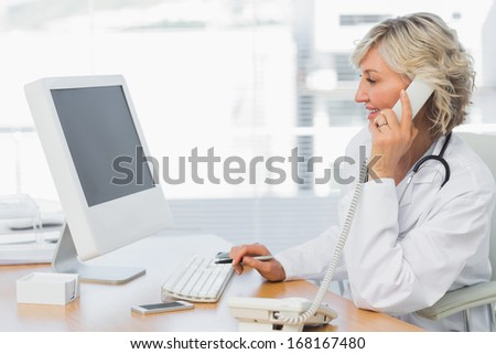 Side view of a smiling female doctor using phone and computer at desk in medical office - stock photo