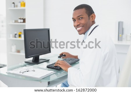 Side view of a smiling male doctor using computer at medical office