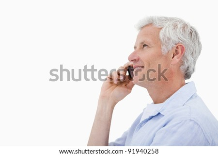 Side view of a smiling mature man making a phone call against a white background