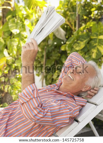 Side view of a smiling mature man reclining on lounge chair and reading newspaper - stock photo