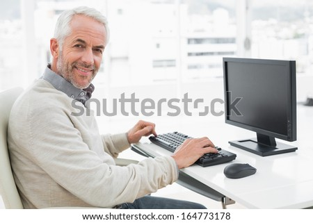 Side view of a smiling mature man using computer at desk in a bright office