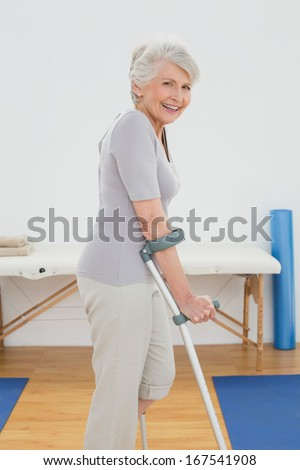 Side view of a smiling senior woman with crutches standing in the hospital gym - stock photo