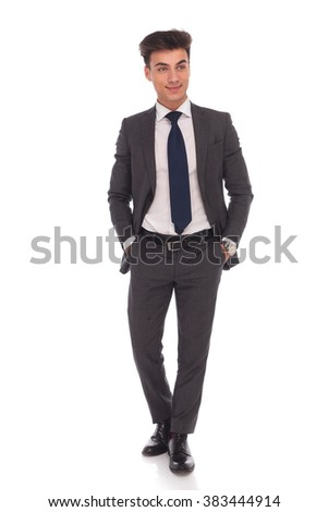 side view of a smiling young business man standing with his hands in pockets and looks away from the camera on white background - stock photo