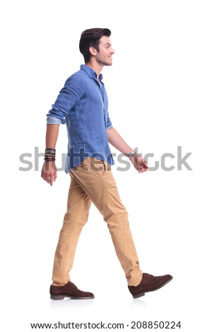 side view of a smiling young casual man walking , on white background - stock photo
