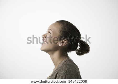 Side view of a smiling young woman looking up against gray background - stock photo