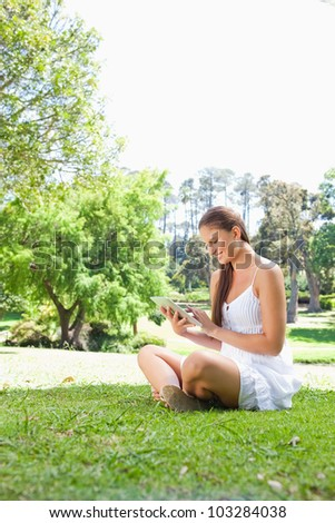 Side view of a smiling young woman on the lawn with a tablet computer