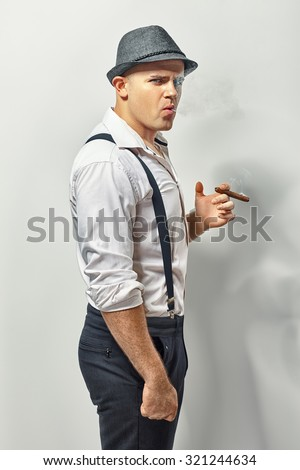 Side view of a stylish young man smoking cigar   - stock photo