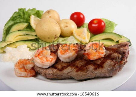 "Side view of a ""surf and turf"" meal of ""New York steak"" and prawns with a salad"