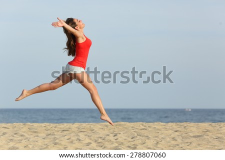 Side view, of a teen girl wearing red shirt and shorts jumping happy on the beach - stock photo