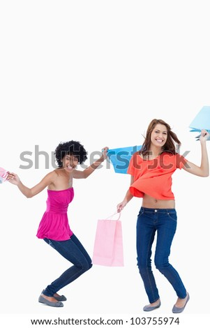 Side view of a teenage slightly flexing her legs while her friend is standing up - stock photo