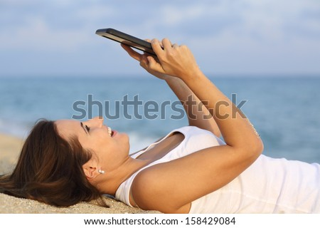 Side view of a teenager girl laughing and browsing her tablet pc lying on the sand of the beach - stock photo
