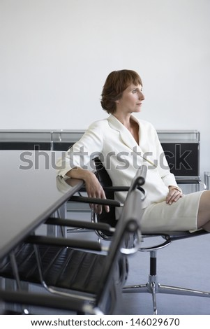 Side view of a thoughtful businesswoman sitting against table in conference room - stock photo