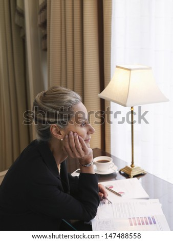 Side view of a thoughtful middle aged businesswoman sitting with documents at home office desk - stock photo