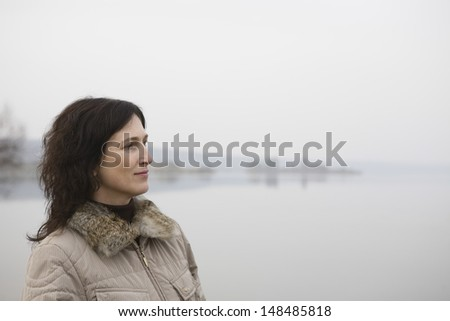 Side view of a thoughtful woman standing near the lake - stock photo