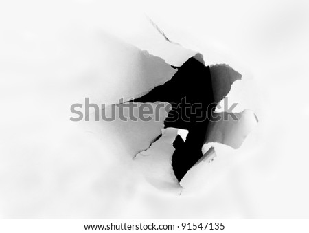 Side view of a torn jagged hole in paper - stock photo