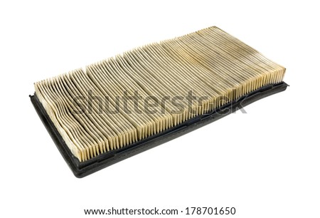 Side view of a used and dirty automobile air filter on a white background.