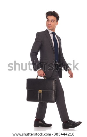 side view of a walking businessman looking back over his shoulder while holding a suitcase on white background - stock photo