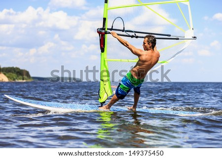 Side view of a windsurfer passing by - stock photo