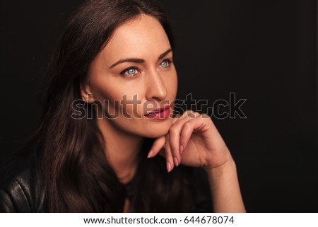 side view of a woman dreaming away on black background