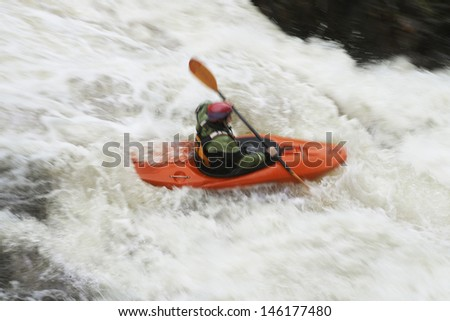 Side view of a woman kayaking in rough river - stock photo