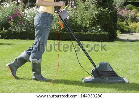 Side view of a woman mowing the lawn with electric mower