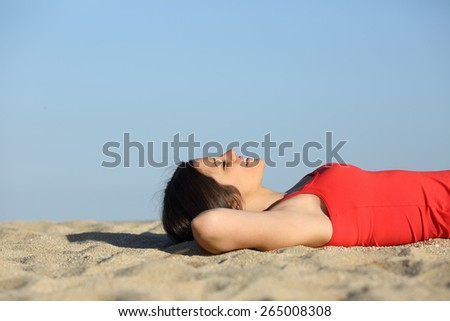 Side view of a woman resting and relaxing on the beach lying on the sand - stock photo
