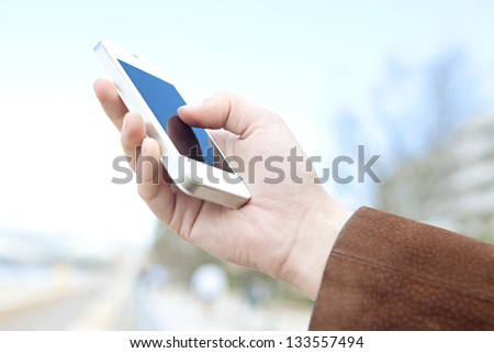 Side view of a woman's hand holding a modern slick smartphone while dialing with her thumb against a blue background. - stock photo