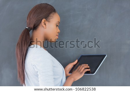 Side view of a woman using a tablet computer in a classroom - stock photo