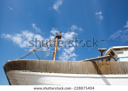 Side view of a wooden fishing boat under construction in shipyard in the harbour of Essaouira against a blue clear sky, Morocco. - stock photo