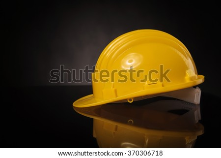 side view of a yellow construction safety  helmet on a black table with reflexion - stock photo